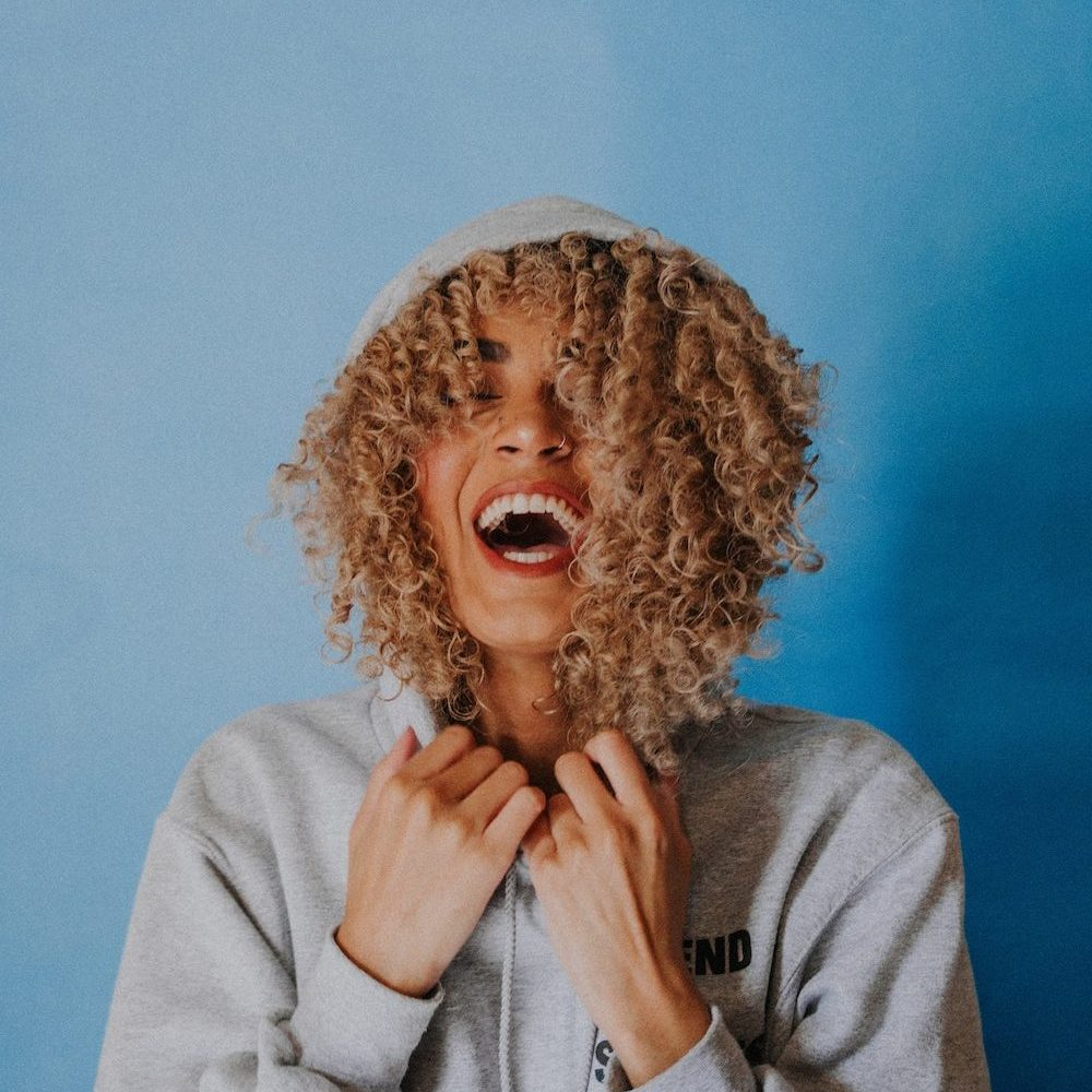 woman in a hoodie laughing