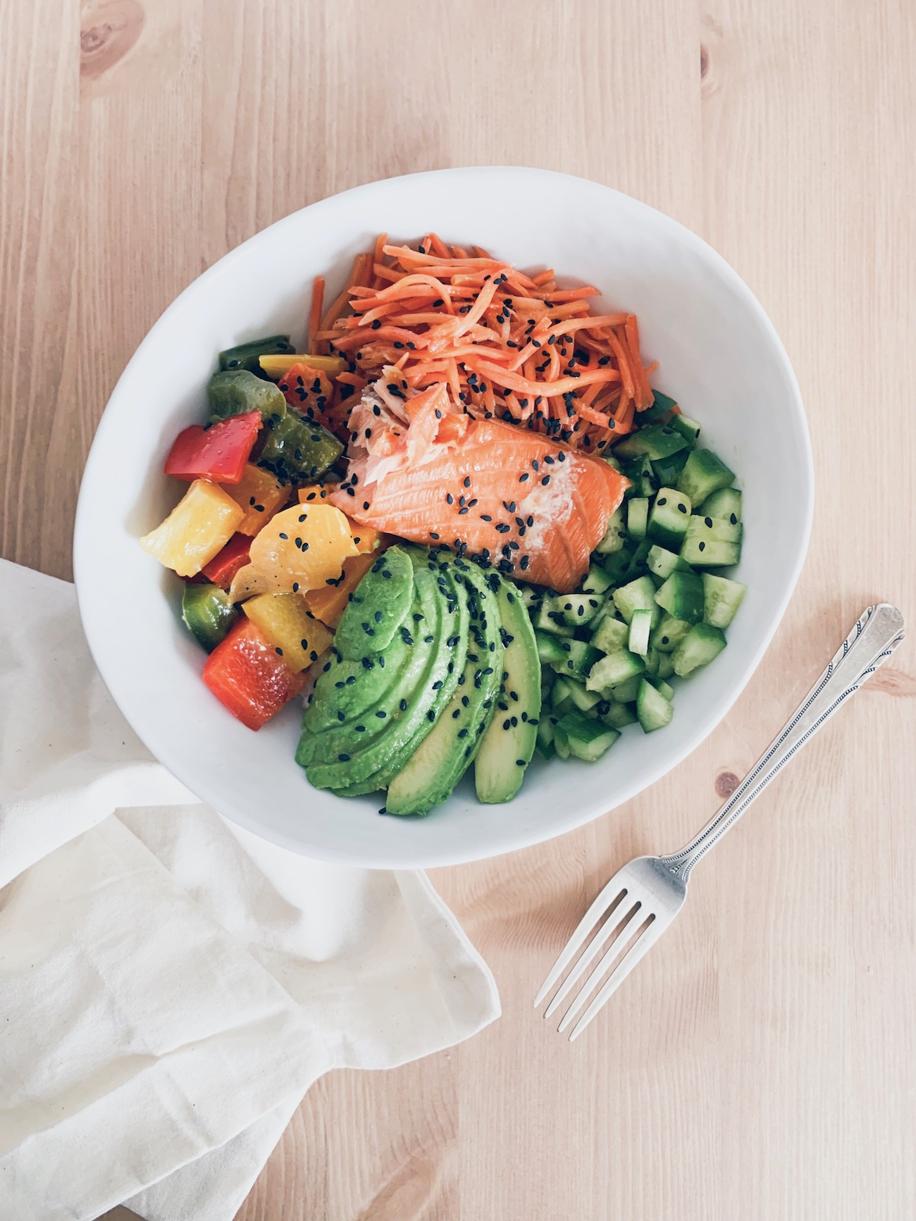 A colorful sushi bowl with black sesame seeds