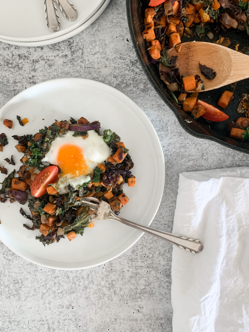Plate of healthy breakfast hash with egg on top