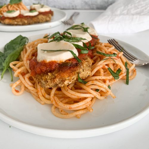 Gluten-free chicken parmesan over spaghetti and marinara with fresh basil