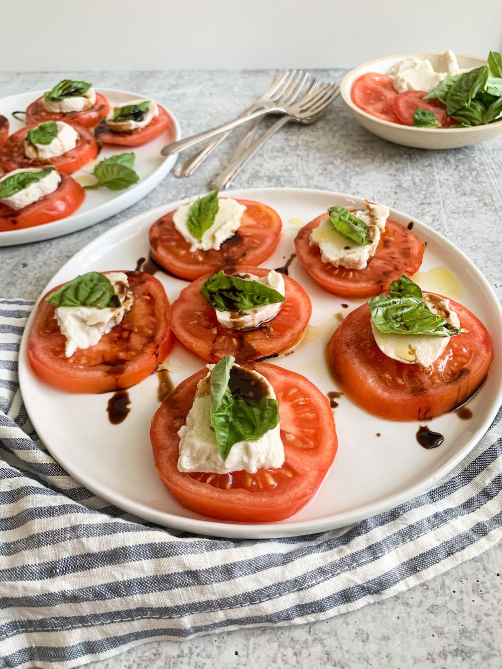 vegan mozzarella cheese on tomato slices with fresh basil