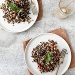 plates of black lentil salad with rice and vegetables