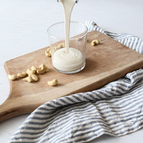 pouring cashew cream into a cup
